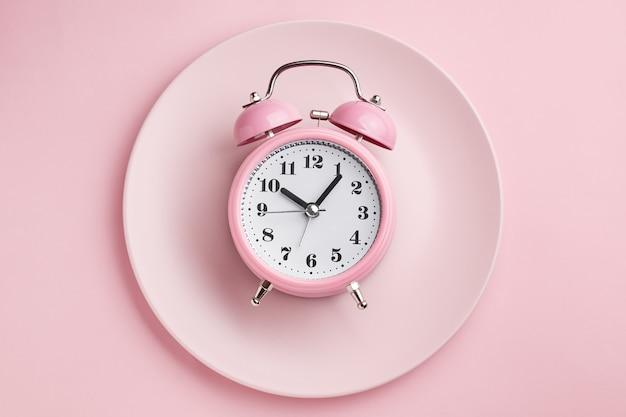 Wekker op lege roze plaat. concept van intermitterend vasten, lunch, dieet en gewichtsverlies