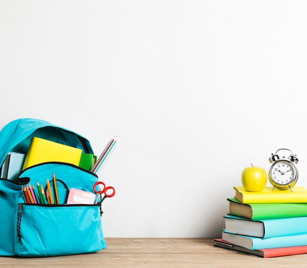Wekker op stapel boeken en goed ingepakte schooltas met benodigdheden