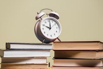 Wekker op stapel van boekenrek tegen gekleurde achtergrond