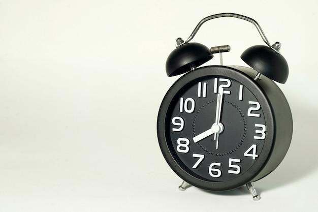 Wekker op wit, met tijd om 8 uur, het is nu laat.