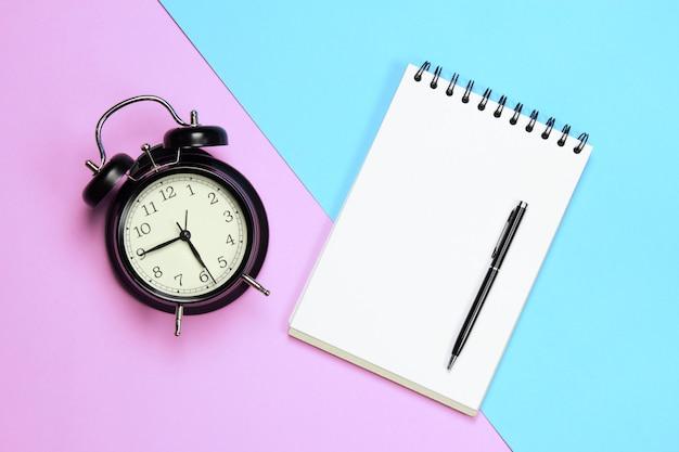 Wekker papieren pen op roze en blauwe achtergrond in concept kladblok en ontspannen tijd voor werk