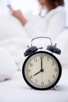 Wekker staande op nachtkastje gaan ring vroege ochtend om wakker vrouw in bed.