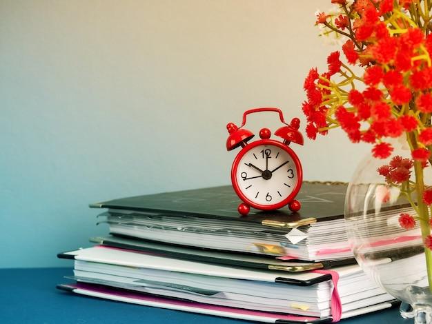 Wekker staande op tafel door stapel boeken tegen effen achtergrond.