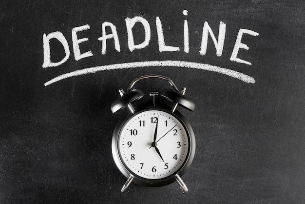 Wekker tegen schoolbord met deadline tekst