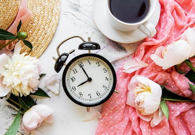 Wekker, thee en pioenrozen