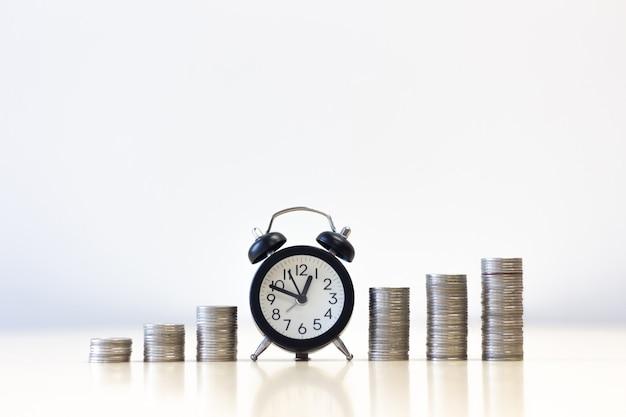 Wekker verhoging van geld munten stap stap groeiende groei geld te besparen.