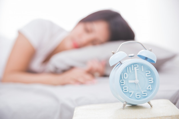 Wekker vooraan vrouwenslaap op een bed