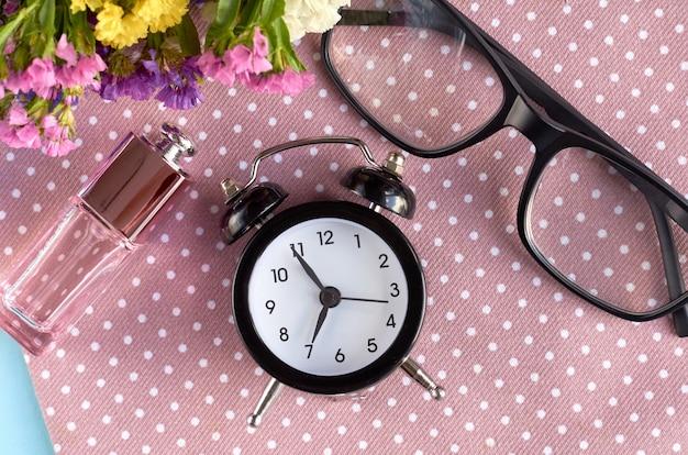Wekker, zwarte bril en parfumfles op servetoppervlak.