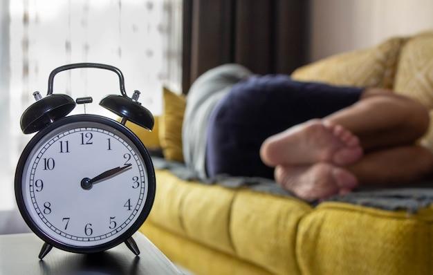 Wekkerclose-up en een slapende man.