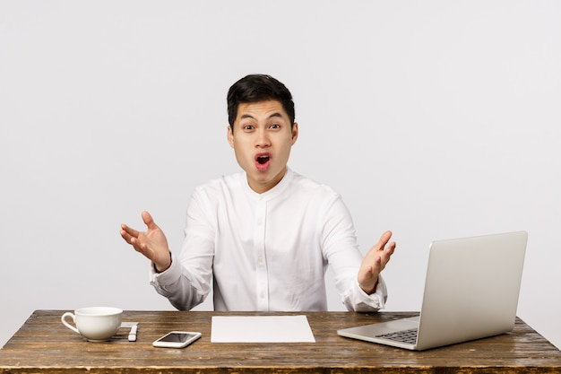 Wel verdomme. gefrustreerd en geschokt, verrast jonge aziatische man op kantoor, zit bureau gespreid handen zijwaarts in ontzetting en teleurstelling, hijgend naar de kaak schudde, hoorde onbevredigend nieuws