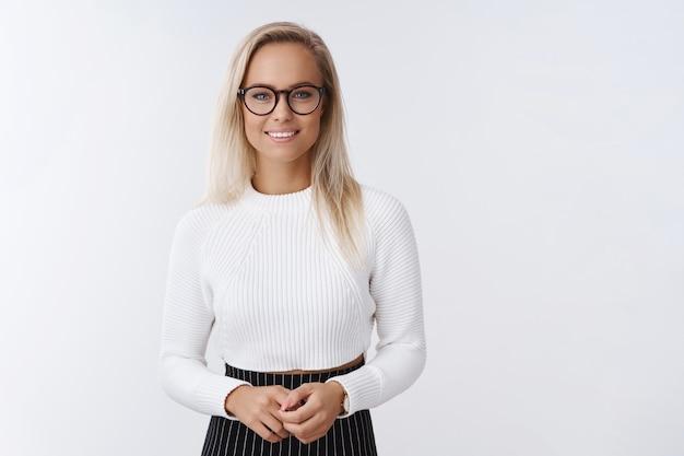 Welgemanierde elegante blonde vrouwelijke projectmanager die tijdens de lezing praat over plannen en prestaties bedrijf handen aanraken en vriendelijk glimlachen naar de camera die de ogen van het publiek over de witte muur trekt.