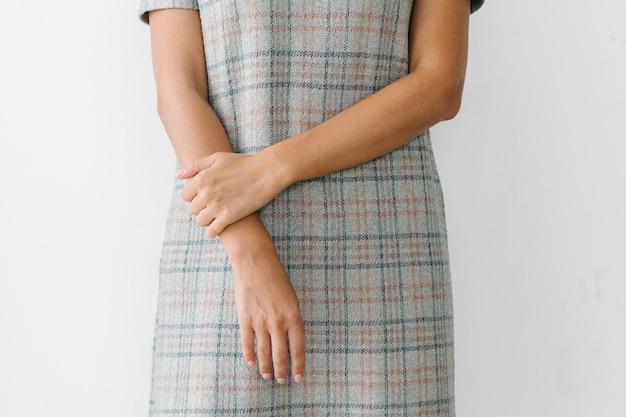 Welgemanierde vrouw die een geruite jurk draagt