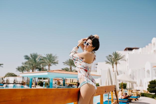 Welgevormd dromerig meisje in zwembroek en zonnebril wegkijken en wachten op vrienden om samen in het zwembad te zwemmen. portret van gebruinde slanke jonge vrouw die van exotisch landschap met palmbomen geniet