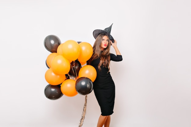 Welgevormd vrouwelijk model dat in heksenhoed vóór halloween-partij glimlacht