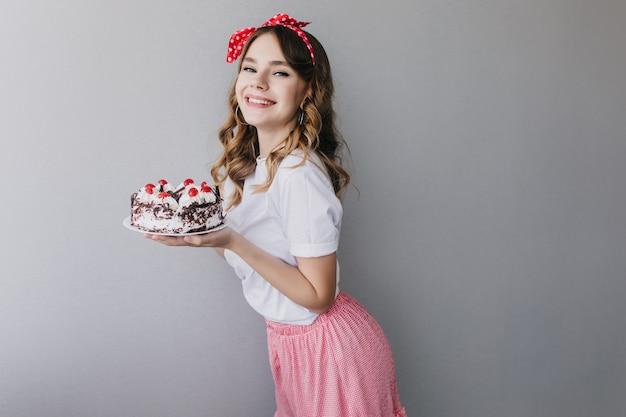 Welgevormd vrouwelijk model met rood lint dat zoete pastei houdt. binnen schot van blithesome krullende vrouw met verjaardagstaart.
