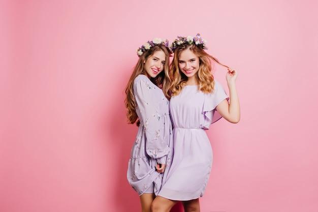 Welgevormde blonde dame in korte jurk spelen met haar terwijl poseren in de buurt van zus