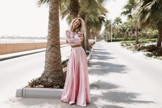Welgevormde blondine naast de zee in dubai, palmbomen, hete, prachtige jurken, zomerse zonnige lifestyle mode fotograferen, zwaaien in de wind jurk, kalm en chillen bij het zwembad, kapsel, make-up
