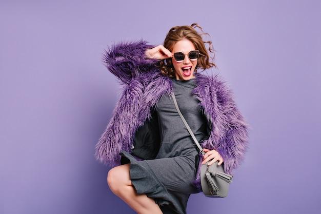 Welgevormde donkerharige meisje in paarse bontjas met plezier in de studio