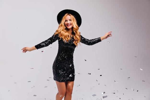 Welgevormde extatische vrouw in zwarte jurk dansen in. binnenfoto van debonair glamoureus meisje in hoed geïsoleerd op een witte muur.