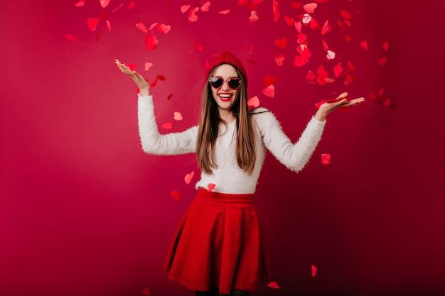 Welgevormde glamoureuze vrouw in zonnebril dansen op feestje