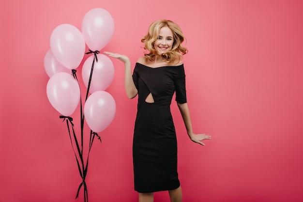 Welgevormde jonge blanke vrouw in lange jurk met plezier met feestballonnen. prachtig europees meisje poseren met opwinding op helder roze muur.