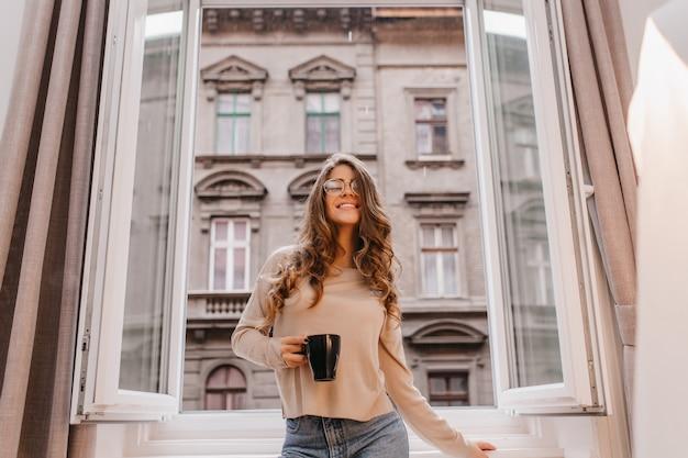 Welgevormde jonge vrouw draagt een bril poseren met plezier in de buurt van venster