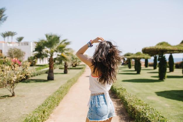 Welgevormde langharige meisje in wit overhemd wandelen op de palm steegje onder blauwe hemel in zonnige ochtend. portret van stijlvolle jonge dame grappig dansen in park op resort in zomervakantie.
