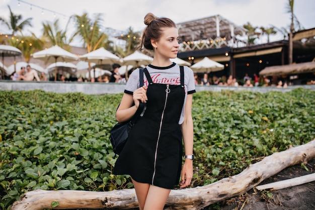 Welgevormde meisje draagt trendy kleren staan in de buurt van gazon en wegkijken. openluchtportret van knappe kaukasische dame die in stad koelen.