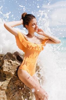 Welgevormde meisje poseren met plezier buiten met getijdenboring. verbazingwekkende gebruinde dame die lacht en luistert naar zeegeluiden.