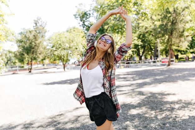 Welgevormde mooie vrouw die op aard lacht. verfijnd meisje in glazen die in park dansen.