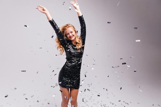 Welgevormde opgewonden meisje chillen op feestje. vrolijke blonde vrouw in trendy zwarte jurk positieve emoties uitdrukken.