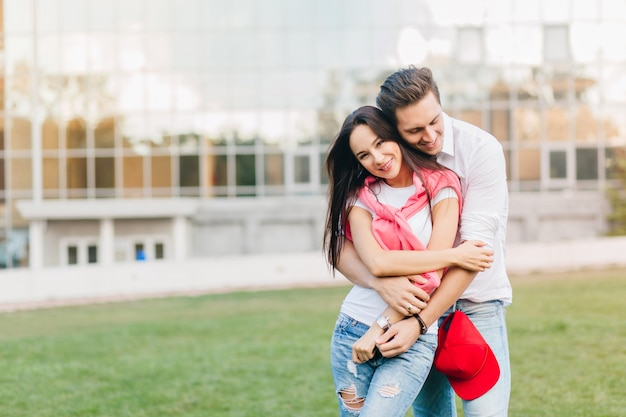 Welgevormde vrouw in blauwe jeans in polshorloge huggs met echtgenoot dichtbij gazon voor gebouw