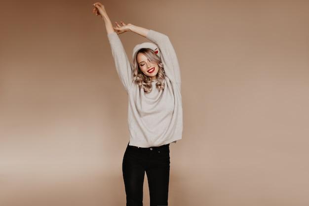 Welgevormde vrouw in bruine trui die zich uitstrekt in de studio