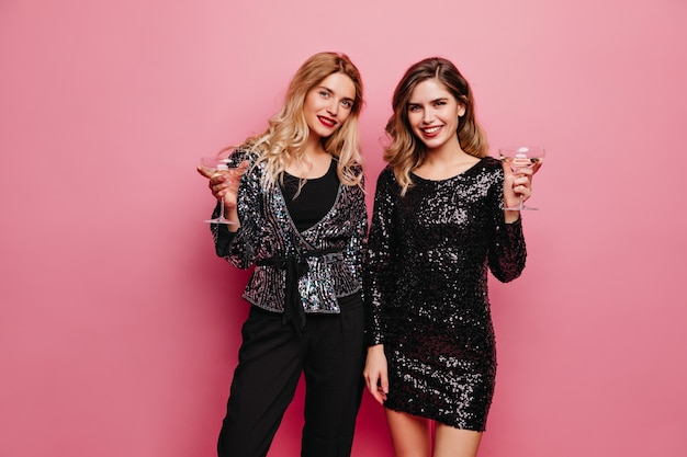 Welgevormde vrouw in trendy sparkle jurk tijd doorbrengen op feestje. extatische vriendinnen genieten van fotoshoot en drinken van wijn.