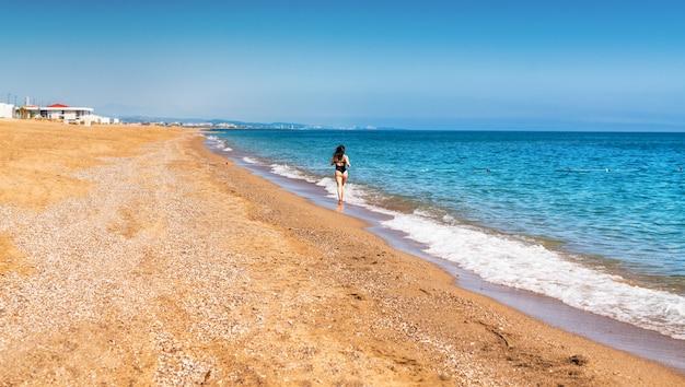 Welgevormde vrouw in zwembroek joggen langs een tropisch strand