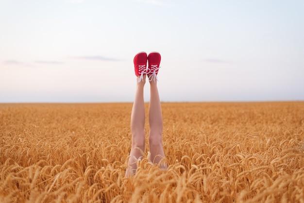 Welgevormde vrouwelijke benen steken uit een tarweveld. vegetarisch concept.