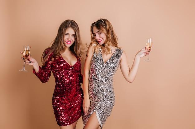 Welgevormde vrouwen in glamoureuze kleding poseren met glazen wijn op lichte muur