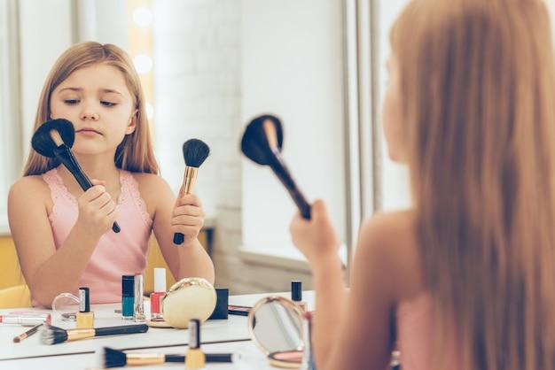 Welke borstel is beter? schattig klein meisje dat een van de twee make-upborstels kiest terwijl ze aan de kaptafel zit