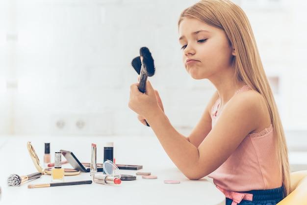 Welke borstel moet ik kiezen? zijaanzicht van peinzend klein meisje dat een van de twee make-upborstels kiest terwijl ze aan de kaptafel zit