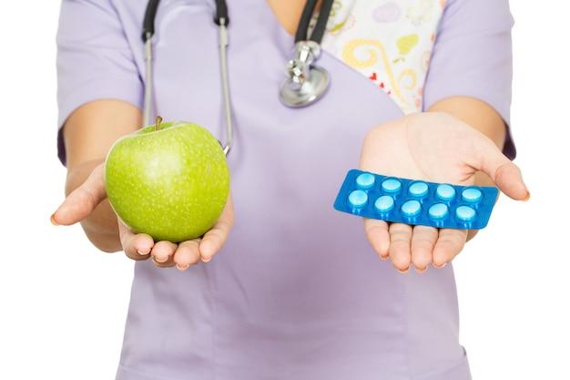 Welke kies je? bebouwde close-up van een vrouwelijke arts die een appel en pillen houdt om in haar handen te kiezen