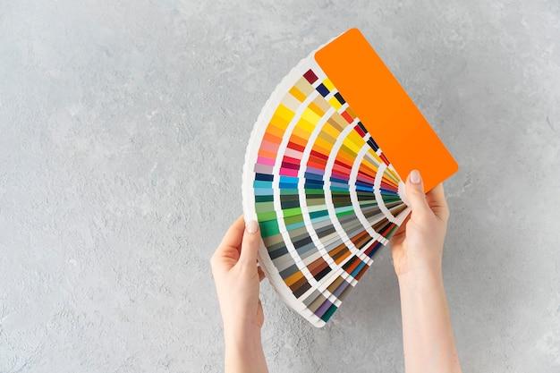 Welke kleur om het murenconcept te schilderen. vrouwelijke handen met kleurenpalet ventilator