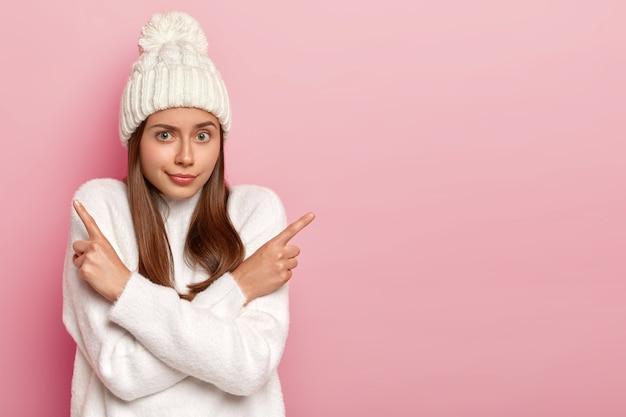 Welke te kiezen. aarzelende natuurlijke europese vrouw wijst zijwaarts, kruist armen over de borst, suggereert twee varianten, neemt een beslissing, draagt warm witte trui en hoed, lege ruimte op roze achtergrond
