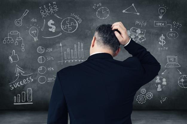 Welke weg zal ik kiezen? achteraanzicht van een peinzende volwassen man die zijn hoofd krabt en kijkt naar digitaal samengestelde zakelijke borden en grafieken op schoolbord