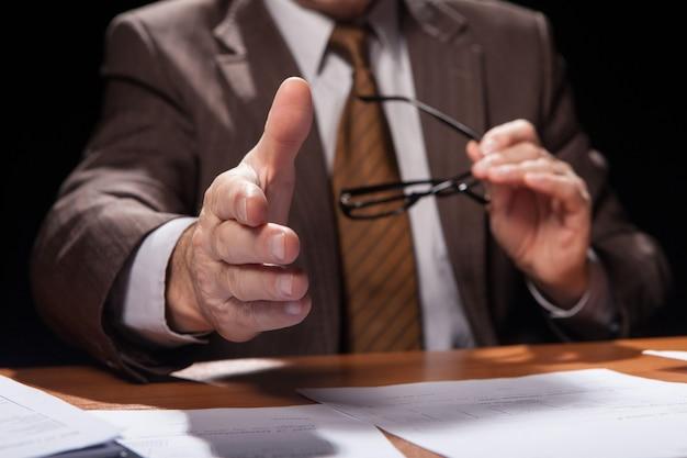 Welkom aan boord. bijgesneden afbeelding van een man in formalwear die op zijn werkplek zit en zijn hand uitstrekt om te schudden terwijl hij geïsoleerd is op een zwarte achtergrond