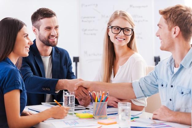 Welkom aan boord! groep vrolijke zakenmensen die samen aan tafel zitten terwijl twee mannen handen schudden en glimlachen