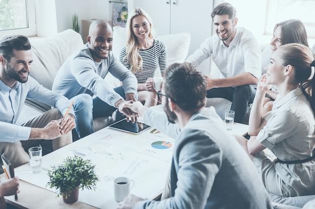 Welkom aan boord! groep zelfverzekerde zakenmensen die samen aan het bureau zitten terwijl twee mannen handen schudden en glimlachen