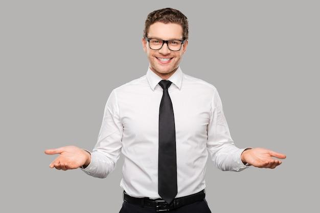 Welkom aan boord! knappe jonge man in overhemd en stropdas die zijn armen uitstrekt en glimlacht terwijl hij tegen een grijze achtergrond staat