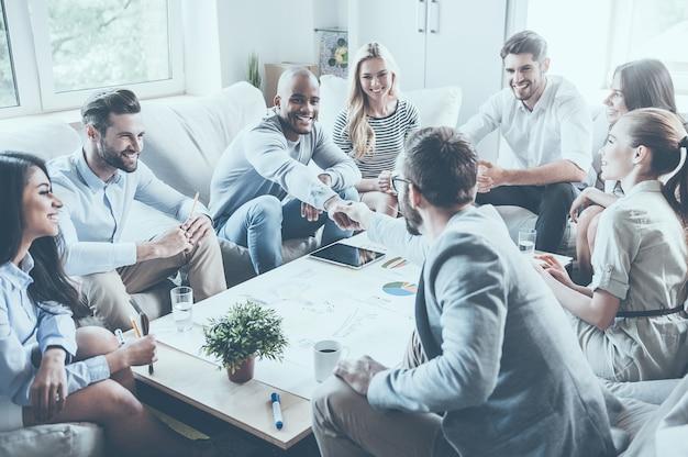 Welkom bij team! groep zelfverzekerde zakenmensen die samen aan het bureau zitten terwijl twee mannen handen schudden en glimlachen