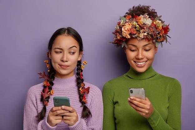 Welkom herfst. nieuwsgierige aziatische vrouw met twee vlechten versierd met herfstbladeren en bessen, gebruikt cellulair, gluurt naar vrienden-gadget. h.