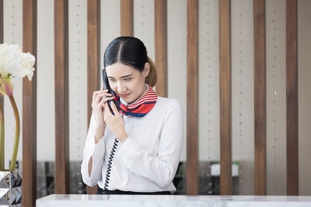 Welkom in het hotel, gelukkige jonge aziatische vrouw hotelreceptionist werknemer glimlachend permanent, ze neemt telefoontje bij een moderne luxe receptiebalie te wachten op gasten krijgen sleutelkaart in hotel